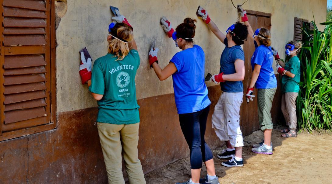 Voluntarios de Construcción retirando pintura vieja de una pared.